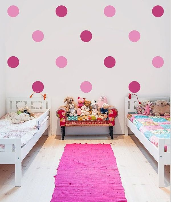 Giant pink polka dot wall stickers on a white wall in a little girls' shared bedroom space